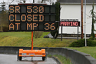 """A highway sign warns of the road closed by the mudslide while a sign on a church in the background reads """"keep praying"""" in Arlington, Washington March 28, 2014.  Rescue officials said the death toll from a catastrophic mudslide in Washington state is soon expected to climb far higher, as some residents voiced anger that they were prevented from helping in the initial disaster response six days ago.   REUTERS/Rick Wilking (UNITED STATES)"""