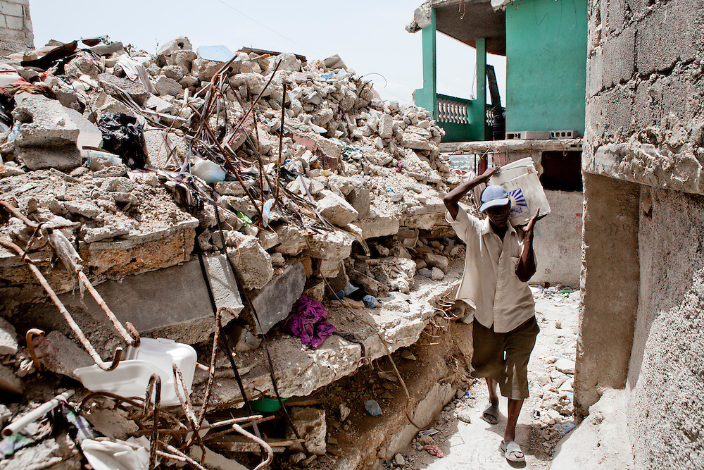 PORT-AU-PRINCE, HAITI - JULY 12: Merismo Vital carries a bucket full of debris out of a destroyed house in the Fort National neighborhood on July 12, 2010 in Port-au-Prince, Haiti. Six months after an earthquake killed an estimated 230,000 people, many Haitians are struggling to rebuild their lives. (Photo by Brendan Hoffman/Getty Images) *** Local Caption *** Merismo Vital