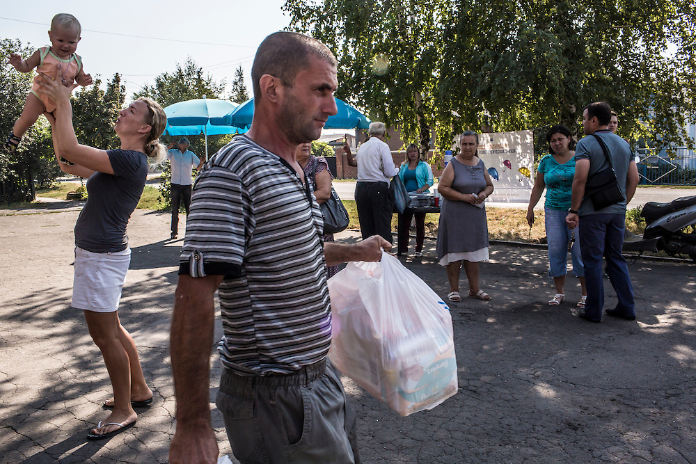 SARTANA, UKRAINE - AUGUST 29, 2015: A man carries bags of staple products such as flour and diapers for another resident during distribution of humanitarian aid in Sartana, Ukraine. The village of Sartana, on the northeastern outskirts of Mariupol, has been relatively close to the front line between Ukrainian and pro-Russian rebel forces, with many incidents of shelling damaging homes and injuring or killing civilians. CREDIT: Brendan Hoffman for The New York Times