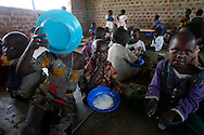 October 6, 2006 - Children eat porridge at a day care center in Coope camp for internally displaced people, or IDP, near Gulu in north Uganda. Coope, with a population of 18,000, is one of 76 IDP camps around Gulu, the main base for the Uganda Peoples Defense Force fighting the insurgent Joseph Kony's Lord's Resistance Army. Kony's LRA movement has been fighting for the past 20 years to force the East African country to be ruled according to the Christian Ten Commandments. Over 2 million people, mostly of the Acholi tribe, have moved or were forced to move from their villages to camps close to the towns of Gulu, Lira, and Kitgum where they are watched over by the Ugandan Army. The LRA rebels have abducted thousands of children and have forced them to fight against the Ugandan Army and the Acholi people. Current peace talks between Kony's LRA and the Ugandan government held in Juba, southern Sudan, offer a glimpse of hope to ending this ongoing conflict..(Photo by Jakub Mosur/Polaris)<br />