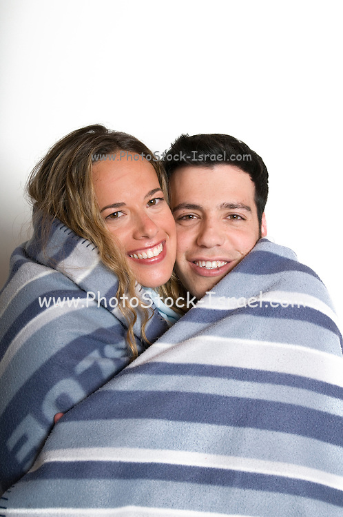 A young romantic couple in their 20s wrapped together in a blanket on a white background Model Releases available