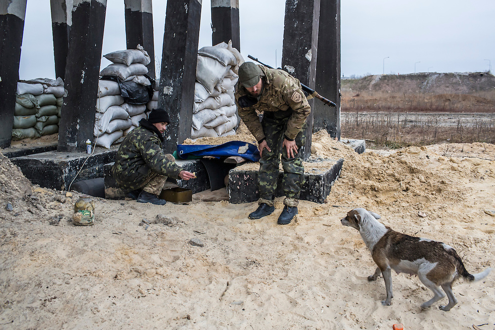 "PERVOMAISKE, UKRAINE - NOVEMBER 17, 2014: ""Patrick,"" left, and Grigoriy Matyash, right, of the 5th platoon of the Dnipro-1 brigade, a pro-Ukraine militia, call a stray dog that recently gave birth to puppies at their post underneath a bridge in Pervomaiske, Ukraine. CREDIT: Brendan Hoffman for The New York Times"