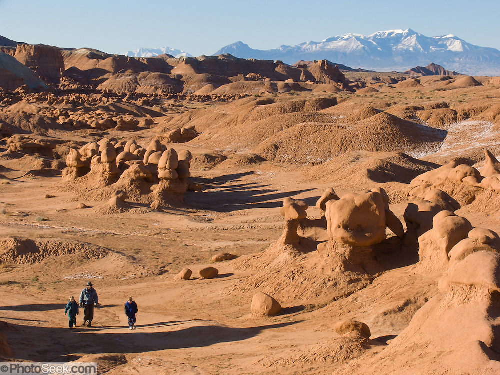 A family with children explores fanciful hoodoos, mushroom shapes, and rock pinnacles in Goblin Valley State Park, in Emery County between the towns of Green River and Hanksville, in central Utah, USA. The Goblin rocks eroded from Entrada Sandstone, which is comprised of alternating layers of sandstone (cross-bedded by former tides), siltstone, and shale debris which were eroded from former highlands and redeposited in beds on a former tidal flat.
