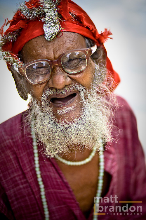 A Muslim fakir or a holy man smiles through his glasses.