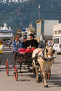 Alaska. Skagway. Visitors enjoy a horse drawn carriage ride throught the streets of Skagway, and the Klondike Gold Rush National Historical Park with  Boardwalks and frontier town facades.