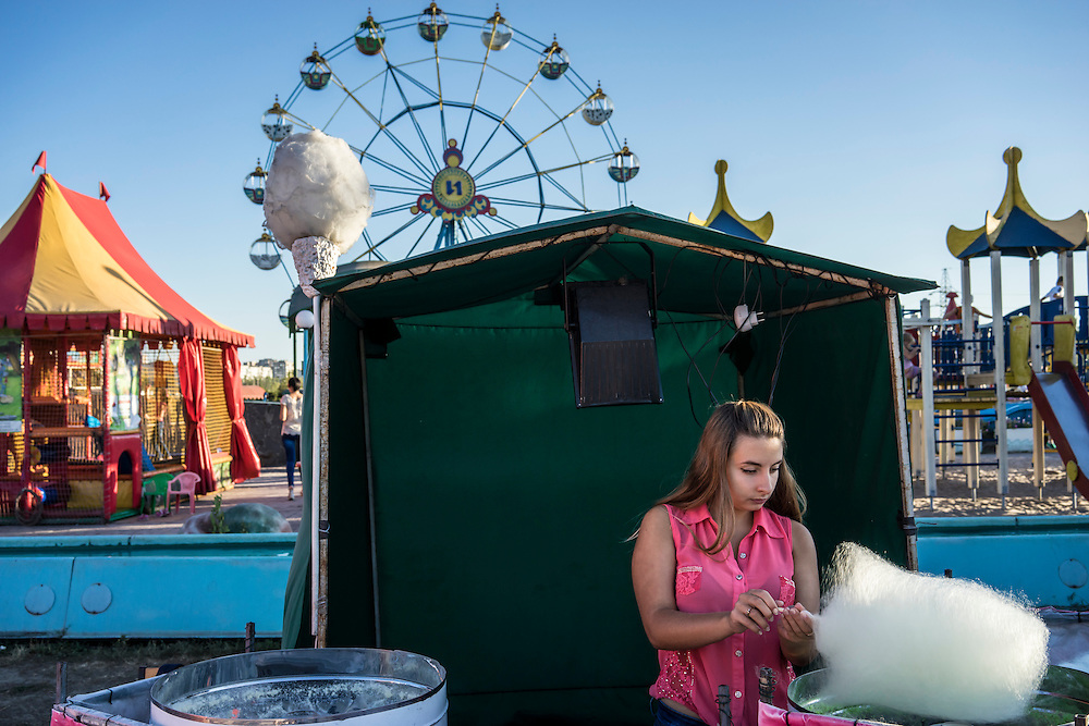 MARIUPOL, UKRAINE - AUGUST 30, 2015: A woman prepares and sells cotton candy at the Mariupol Extreme Park, an amusement park in Mariupol, Ukraine. Despite the front line being a relatively short distance away, Mariupol was lively on a warm summer weekend, with little evidence that people expect the fighting to advance this far. CREDIT: Brendan Hoffman for The New York Times