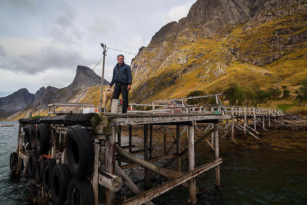 A man stands alone on the pier at Rostad, Moskenesoya, Lofoten Islands, Norway.