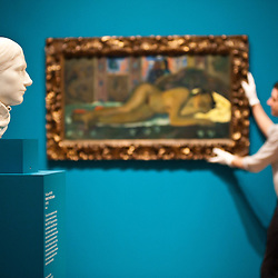 London, UK - 19 June 2013: ?Portrait of Mette Gauguin 1879-1880?, one of only two   marble   sculptures ever   created by the artist stands in the room while an art technician called Jack works on a canvas entitled ?Nevermore 1897? by Paul Gauguin