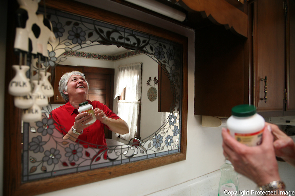 Farm wife Karen Johnson reaches for a bottle of vitamins in the kitchen of her home in rural Shelby County, Iowa.  The Johnson's take a daily dosage of vitamin E, vitamin C, Calcium, Gluconosime and a low dosage aspirin to help stay healthy.<br /> <br /> Johnson and her husband Bill have been farming for over 55 years, and have no immediate plans for retirement.  <br /> <br /> &quot;We plan on doing this for another 15 years,&quot; she said.    Photo by David Peterson