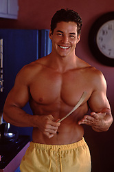 muscular man in the kitchen holding a wooden spoon