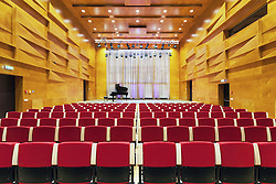 Concert hall auditorium, with rows of seats. Heino Eller's Tartu Music School in Estonia. Large window, curtain.