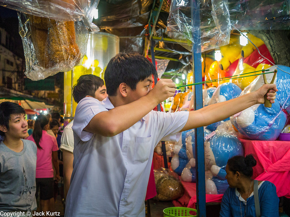 "27 NOVEMBER 2012 - BANGKOK, THAILAND: A man shoots a sling shot at targets in a booth on the midway at the Wat Saket Temple Fair in Bangkok. Wat Saket, popularly known as the Golden Mount or ""Phu Khao Thong,"" is one of the most popular and oldest Buddhist temples in Bangkok. It dates to the Ayutthaya period (roughly 1350-1767 AD) and was renovated extensively when the Siamese fled Ayutthaya and established their new capitol in Bangkok. The temple holds an annual fair in November, the week of the full moon. It's one of the most popular temple fairs in Bangkok. The fair draws people from across Bangkok and spills out in the streets around the temple.    PHOTO BY JACK KURTZ"
