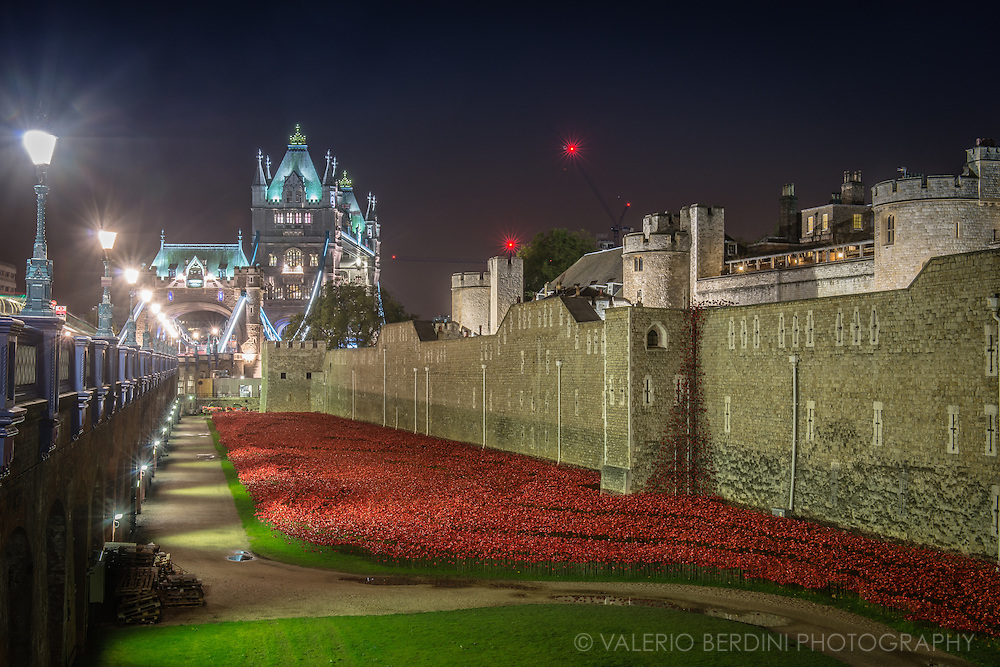 Tower Bridge seen through the Tower of London passageway decorated with Blood Swept Lands and Seas of Red Installation. This is an evolving installation marking the centenary of the outbreak of the First World War. Created by ceramic artist Paul Cummins, with setting by stage designer Tom Piper, 888,246 ceramic poppies will progressively fill the Tower's famous moat.