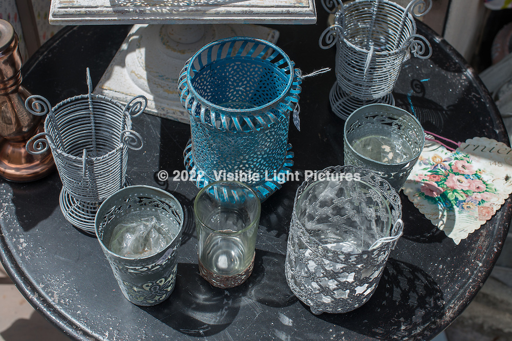 A collection of assorted candle holders on display in front of a shop in Gordes.