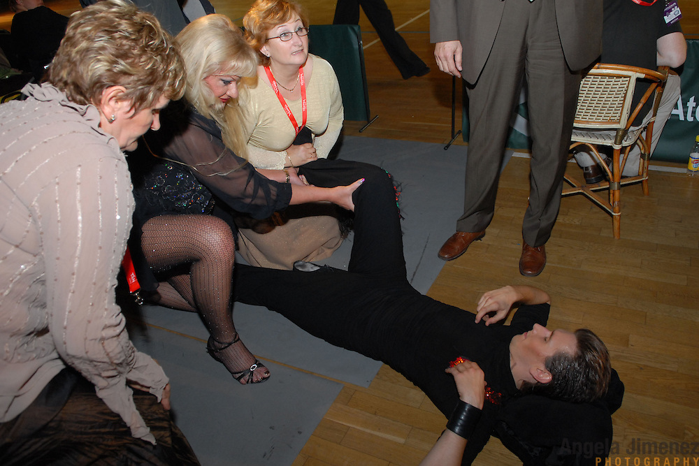 "Defending World Champion same-sex ballroom dancer Gergely Darabos, right, lies on the ground after being overcome with a leg cramp trying to defend his title in the men's Latin division at the 2nd annual World Championship Same-Sex Ballroom Dancing competition at the Korcsarnok arena in Budapest, Hungary, on October 21, 2006. ..Helping him, from left, are his dancing partner's mother, event sponsor Desire (accent on the ""e"") Dubounet and Darbos' mother and father. ..Darabos and his dancing partner, Robert Tristan Szelei, won the men?s Standard division and went on to finish fourth in the Latin division, after Darabos recovered from the cramp. ..The dance couple, known as the ""Black Swans,"" have been training and preparing to host the 2nd annual World Championship and the Csardas Cup, the first-ever Eastern European same-sex ballroom competition. This is the pinnacle event of the blossoming same-sex ballroom scene...The event was organized by the US-based World Federation of Same-Sex Dancing, which hosted the first World Championship Same-Sex championships in 2005 in Sacramento, California. The Black Swans did a large amount of the coordination and planning in Budapest, a city that had never seen an event of this kind. When government funding fell through, they secured funding from patron Dubounet, owner of the local Club Bohemian Alibi. ..The World Championship events are newly recognized, but same-sex dancers have been competing on a national and international circuit for a number of years, especially in Europe, including at the Eurogames, the Gay Games, the London Pink Jukebox Trophy and the Berlin Open, among others. Countries including the United States, the Netherlands, Germany and, now, Hungary, hold their own national same-sex championships. Hungary held its first national championships in April 2006...Szelei and Darabos spent three months at the Sacramento Dancesport same-sex dance school in California this summer, on the first scholarship offered by the Wor"