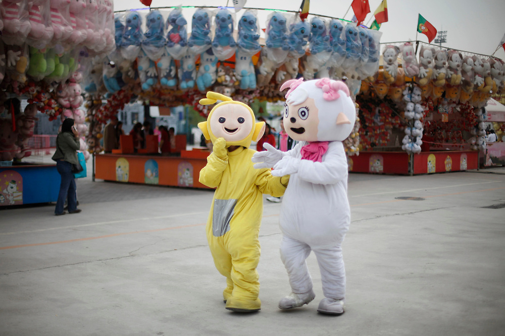Costume characters of a Teletubbie and Pleasant Goat have a chat at a fun fair as the National Day holidays wind down in Beijing, China, Wednesday, Oct. 7, 2009.