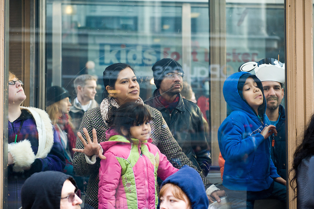 A family watches as the 2012 McDonald's Thanksgiving Parade passes on State Street.