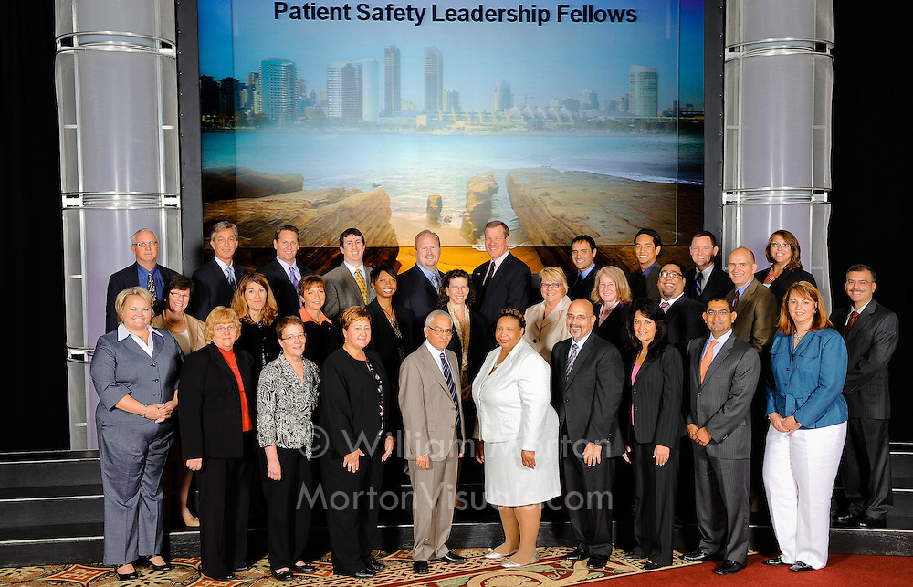 A group portrait during a medical conference shows everyone looking their best in front of a title slide on the projector screen. Event photography at the Manchester Grand Hyatt by Dallas event photographer William Morton of Morton Visuals.