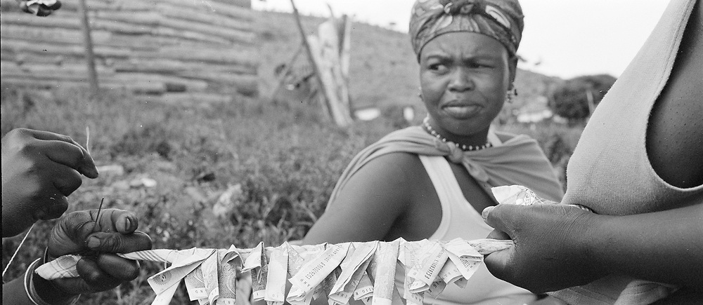 Money as gifts are sewn into a decorative piece for a girl's coming of age ceremony or memulo at Keates Drift, KwaZulu-Natal, South Africa