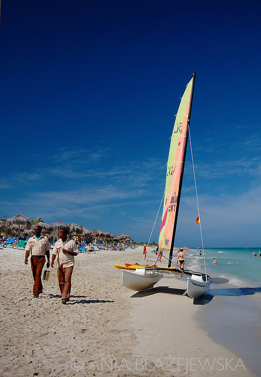 Cuba, Varadero. Catamaran and two walking men on the beach.