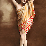 Woman standing in dance pose with Roman or Greek costume. Vintage French erotic Hand tinted realphoto postcard circa 1915