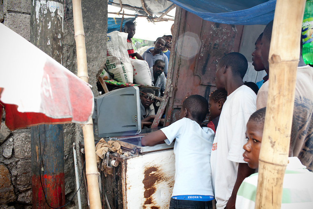 People crowd around a television set to watch Spain play the Netherlands in the World Cup final on July 11, 2010 in Port-au-Prince, Haiti.