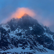 The golden light of sunrise illuminates low clouds hanging at the summit of Mount Isolation, a 1,620-meter (5,315-foot) peak in Fiordland National Park, New Zealand. Located on the southwestern portion of the South Island, Fiordland National Park is New Zealand's largest national park.