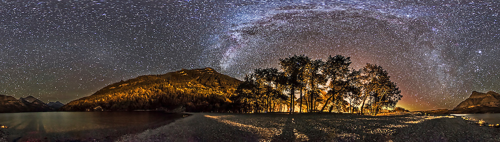 A 360&deg; panorama of the Milky Way and night sky taken at the Cameron Bay picnic area on Upper Waterton Lake in Waterton Lakes National Park, Alberta, Canada. I shot this Sept 21, 2014 on a very clear night with a faint aurora appearing to the north (behind the trees). Streetlights illuminate the scene from behind the trees. Taurus and the Pleiades are rising at right. At left is the faint glow of Gegenschein amid the Zodiacal Band across the dim area of the autumn sky.<br /> <br /> This is a stitch of 8 segments, each shot with the 15mm full-frame fisheye lens, for 1 minute at f/2.8 and with the Canon 6D at ISO 5000. I used PTGui to stitch the segments, with this version being an equirectangular projection.