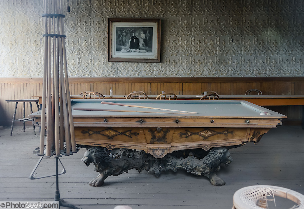 """A billiard table collects dust in the Wheaton & Hollis Hotel at Bodie, California's official state gold rush ghost town. In 1885-86, this building served as the United States Land Office. Later, it was the office for the Power Company, then the Bodie Store, and finally the Hotel. Bodie State Historic Park lies in the Bodie Hills east of the Sierra Nevada mountain range in Mono County, near Bridgeport, California, USA. After W. S. Bodey's original gold discovery in 1859, profitable gold ore discoveries in 1876 and 1878 transformed """"Bodie"""" from an isolated mining camp to a Wild West boomtown. By 1879, Bodie had a population of 5000-7000 people with 2000 buildings. At its peak, 65 saloons lined Main Street, which was a mile long. Bodie declined rapidly 1912-1917 and the last mine closed in 1942. Bodie became a National Historic Landmark in 1961 and Bodie State Historic Park in 1962."""