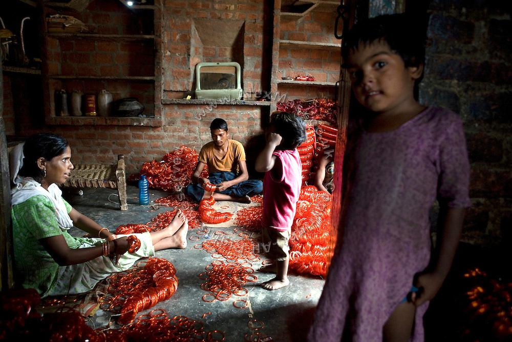 A family home in the slum surrounding Firozabad, renowned as the 'glass city', in Uttar Pradesh, northern India, has been transformed into a small-scale workshop. Due to extreme poverty, over 20.000 young children are employed to complete the bracelets produced in the industrial units. This area is considered to be one of the highest concentrations of child labour on the planet. Forced to work to support their disadvantaged families, children as young as five are paid between 30-40 Indian Rupees (approx. 0.50 EUR) for eight or more hours of work daily. Most of these children are not able to receive an education and are easily prey of the labour-poverty cycle which has already enslaved their families to a life of exploitation. Children have to sit in crouched positions, use solvents, glues, kerosene and various other dangerous materials while breathing toxic fumes and spending most time of the day in dark, harmful environments. As for India's Child Labour Act of 1986, children under 14 are banned from working in industries deemed 'hazardous' but the rules are widely flouted, and prosecutions, when they happen at all, get bogged down in courts for lengthy periods. A ban on child labour without creating alternative opportunities for the local population is the central problem to the Indian Government's approach to the social issue affecting over 50 million children nationwide.