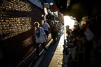 People walk along the sidewalk of a busy street in Buenos Aires, Argentina