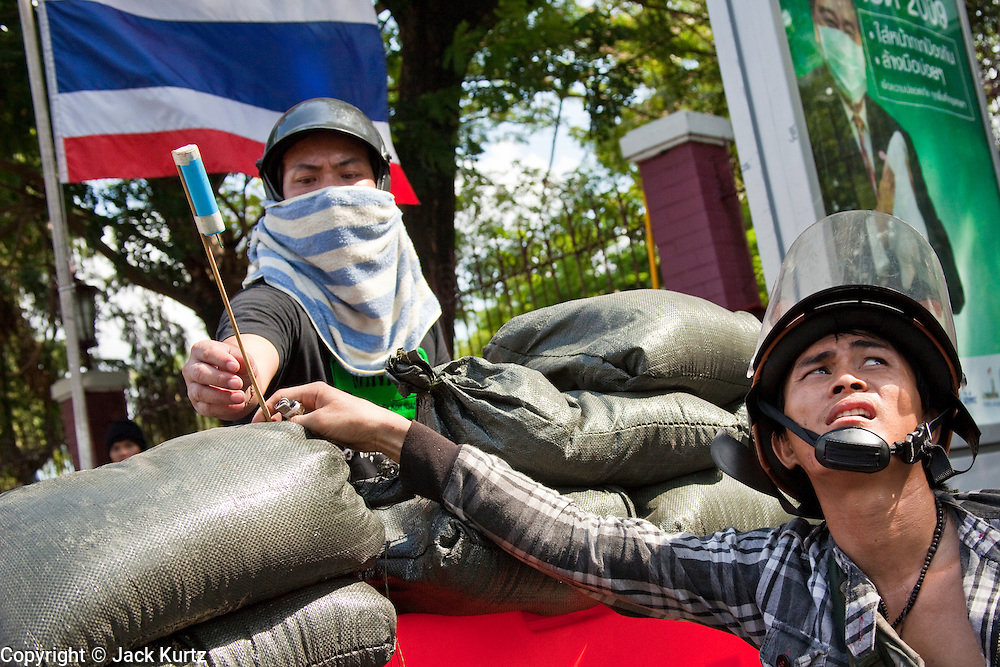14 MAY 2010 - BANGKOK, THAILAND: Red Shirt protesters aim rockets towards Thai military helicopters circling them at the intersection of Rama IV and Witthayu Roads in Bangkok Friday morning. Tensions among Red Shirt protesters demanding the dissolution of the current Thai government rose overnight after Seh Daeng, the Red Shirt's unofficial military leader was shot in the head by a sniper. Gangs of Red Shirts have taken over military checkpoints on Rama IV and are firing small rockets at military helicopters and army patrols in the area. Troops have responded by firing towards posters.  PHOTO BY JACK KURTZ