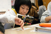 Seattle, Washington: April 7, 2010. English language learner organizes sentences on paper strips, from the text of the novel she's reading, into chronological order during language arts and literacy class.