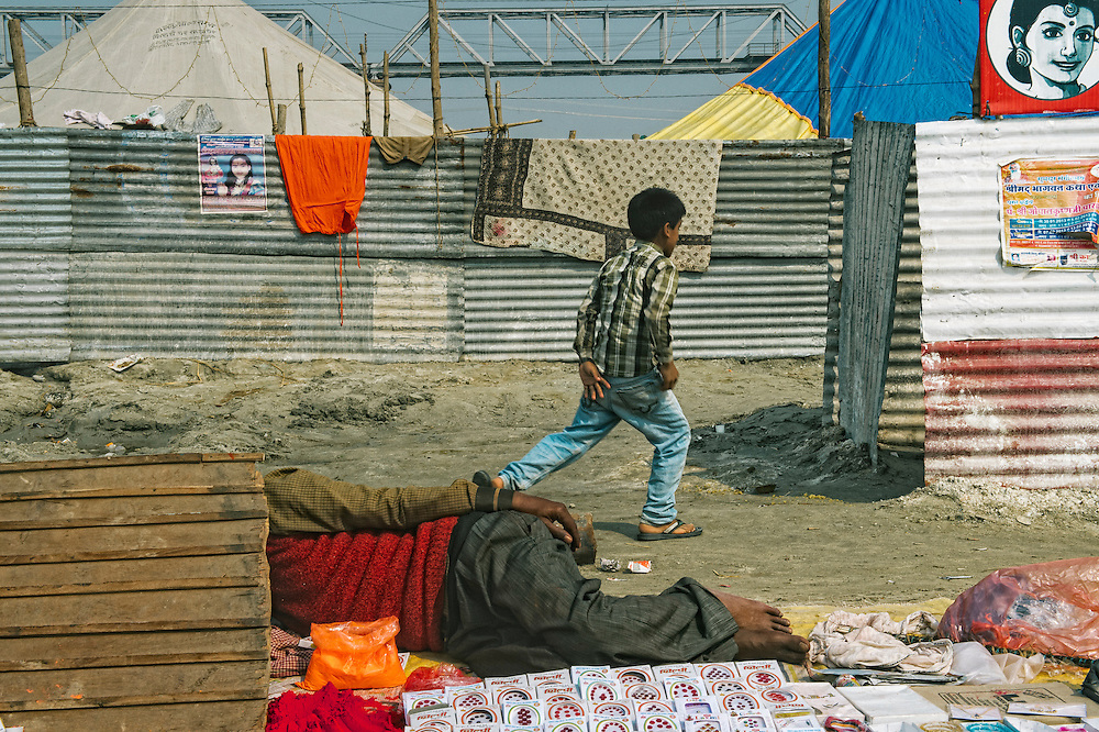 A street side seller taking a nap on a not-so-busy day during the Kumbh Mela in Allahabad.