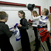 L to R - Kalie ElGersma, Elizabeth Van Roekel and Kayla Lyftogt do a quick change from cheerleader to band member during halftime of their Sept. 19th homecoming game.  Once questioned by a cheerleader coach as to why the girls had to change uniforms, band director Steve Connell suggested wryly that the following week the girls could just cheer in their band uniforms.