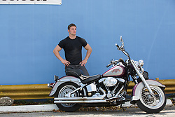 rugged and handsome man with his Harley Davidson Motorcycle outdoors by a colorful wall