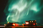 Alaska. Two vehicles pullover along highway to watch the Northern Lights.