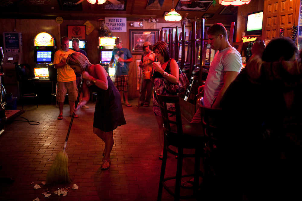 Bartender Londi Ketchum, 24, sweeps up at Arties Sports Bar in Grand Isle, LA on June 23, 2010 where oil has reached land and killed the tourist industry. Manager Frankie Marullo said the bar would be packed with tourists during this time of the year but since the spill business has been slow and closes early.