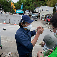Naoki Toyama (wearing blue skip cap and shirt), of a labour workers health and safety NGO, checks air for asbestos pollution levels, in the remains of the town of Onagawa, which was obliterated by the March 11th tsunami, in Onagawa, Tohoku region, Japan, on Friday 17th June 2011. There are now fears for the pollution and health risks that the debris of such towns now holds, including the releasing into the air of asbestos dust.