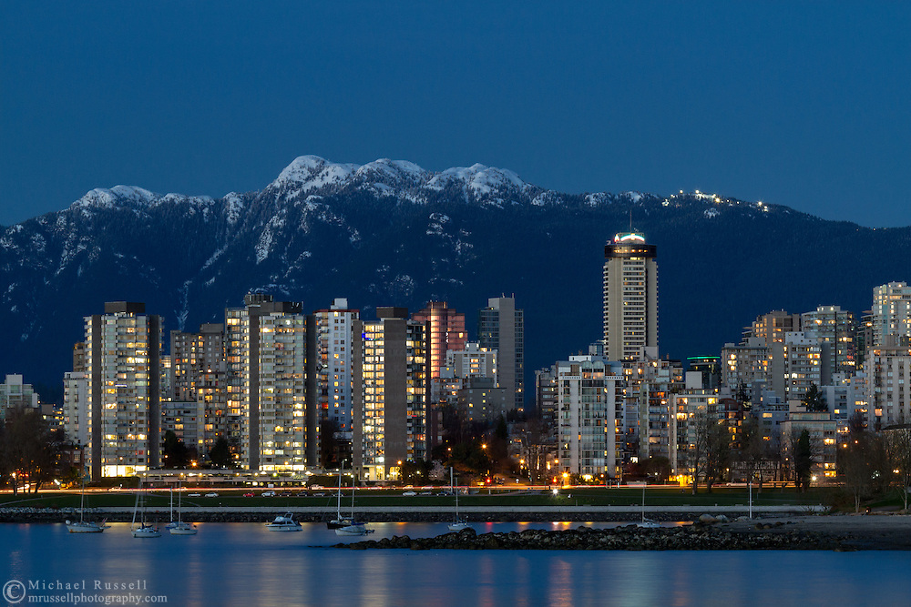 Sunset Beach, Vancouver condo towers, and Mount Seymour in the early evening. The large tower on the right is the Empire Landmark Hotel.  Photographed from Kitsilano Beach Park in Vancouver, British Columbia, Canada