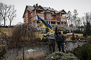 Visitors wave an Ukrainain flag in the garden in front of the lavish mansion Mezhyhirya built by the former President Yanukovych as People roam the sprawling President Yanukovych's countryside residence on February 23, 2014 in Kiev, Ukraine. The 137 hectares residential compound is open to visitors since Feb 22 but all the buildings remain closed.