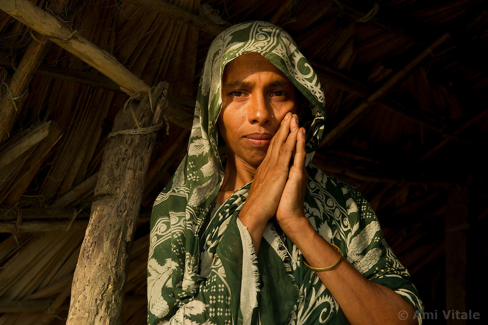 """Mamtaz Begum, 35, stands outside her home in the fishing village of South Tetulbarian in Barguna Sadar upazila  in Bangladesh  October 20, 2010 . Her husband died in a boat accident after capsizing because violent weather. Her mother died later in a cyclone and now she is left with 4 children to feed and very little means to support them. Because of climate change, the seas are getting more violent, less predictable and boats are capsizing more frequently. Twenty percent of the women in this village are widows because so many have lost their husbands in the seas. Coastal and fishing populations are particularly vulnerable and Fishing communities in Bangladesh are subject not only to sea-level rise, but also flooding and increased typhoons. Erosion as a result of stronger and higher tides, cyclones and storm surges is eating away Bangladesh's southern coast.  Yet the largely fishing community cannot live without the sea. """"We only know how to catch fish,"""" say the fishermen. ( Ami Vitale)"""