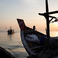 a fishing boat returns to port at dawn, Teluk Bahang, Penang, Malaysia