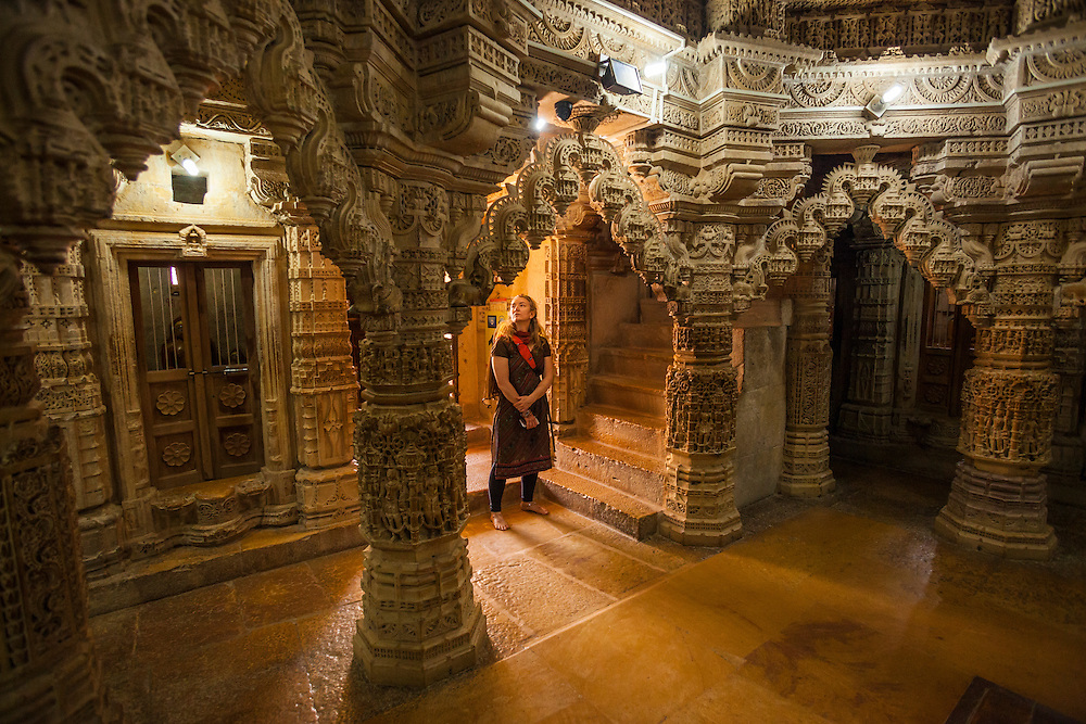 A woman looks at the amazing stone carving within the Jain temple in Jaisalmer Fort, Jaisalmer, Rajashan, India.
