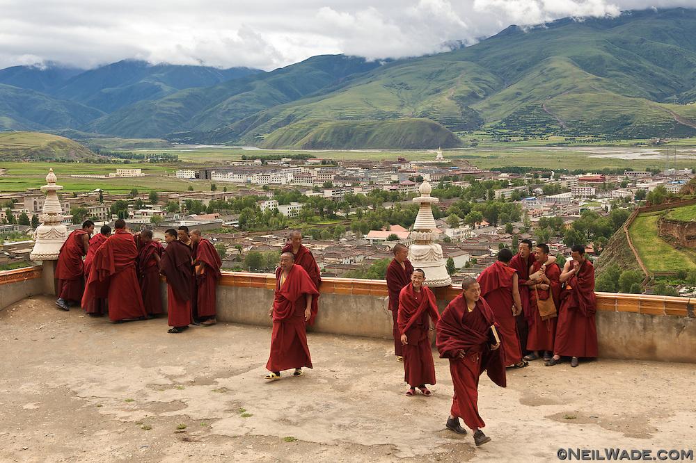 Tibetan Buddhist monks gather before lunch on a balcony overlooking Ganze, Tibet (China).