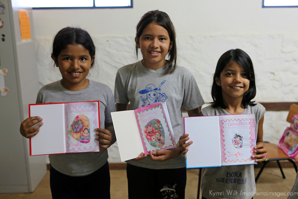 South America, Brazil, Pantanal. Girls share their english notebooks at the primary school at the Caiman Ecological Refuge.