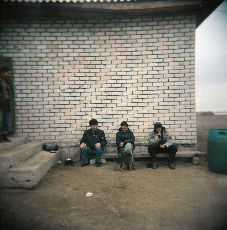 CREDIT: DOMINIC BRACCO II..SLUG:PRJ/KAZAKHSTAN SHEEP HERDERS..DATE:10/22/2009..CAPTION:From left, Talgat Kurmashev, Zhumatai Muzdybayev, and Yeldos (my driver) sit outside near Semey, Kazakhstan. The herders live near an atomic lake which was made during the 1970s as part of an experiment by the USSR to create lakes from atomic bombs. The lake is in an area known as The Polygon, a test site for more than 400 of the Soviet Union's nuclear weapons.