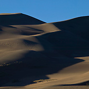 Hikers, visible at the bottom right corner of the image, provide a sense of scale for the Great Sand Dunes near Mosca, Colorado, the tallest sand dunes in North America. The tallest dunes in the park rise about 750 feet from the valley floor.