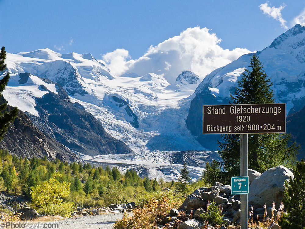 """A sign marks the extent of Morteratsch Glacier in 1920, showing fast retreat. Morteratsch Glacier (Romansh: Vadret da Morteratsch) flows from the Bernina massif in Upper Engadine, Switzerland, the Alps, Europe. From 1878-1998, Morteratsch Glacier retreated 1.8 kilometers (1.1 miles). Melting accelerated to 30 meters (98 feet) per year from 1999–2005. An overwhelming consensus of world scientists agree that global warming is indeed happening and humans are contributing to it through emission of heat-trapping """"greenhouse gases,"""" primarily carbon dioxide (see www.ucsusa.org). Since the industrial revolution began, humans have increased atmospheric CO2 concentration by 35% (through burning of fossil fuels, deforesting land, and grazing livestock). A favorite walk is from Morteratsch (second train stop from Pontresina towards Bernina Pass) to Refuge Boval, which has a restaurant and overnight lodging. The trail is well graded, 5 or 6 miles round trip with 2700 feet gain. Return via lower trail for partial loop. The Swiss valley of Engadine translates as the """"garden of the En (or Inn) River"""" (Engadin in German, Engiadina in Romansh, Engadina in Italian)."""