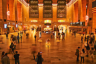 Three ballerinas in white tutu dancing in Grand Central Station at night.